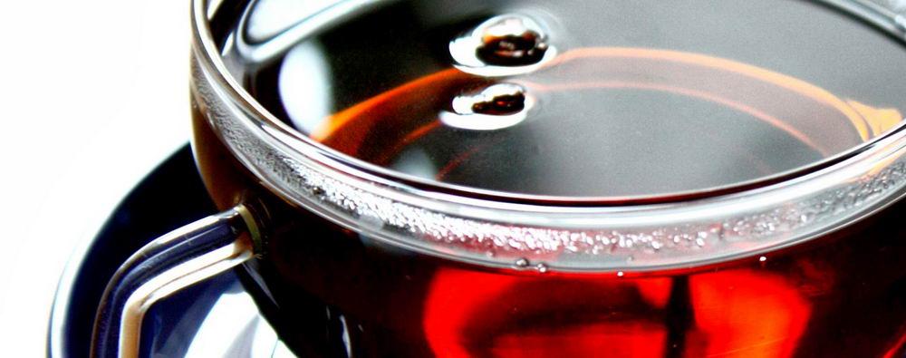 Настой чёрного чая имеет красно-коричневатый оттенок.